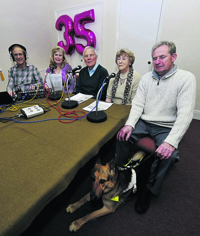 Three readers sit ready to record the news flanked on the left by a recording technician and on the right by a listener and his guide dog. In the background a metallic purple helium balloon in the shape of a 35.