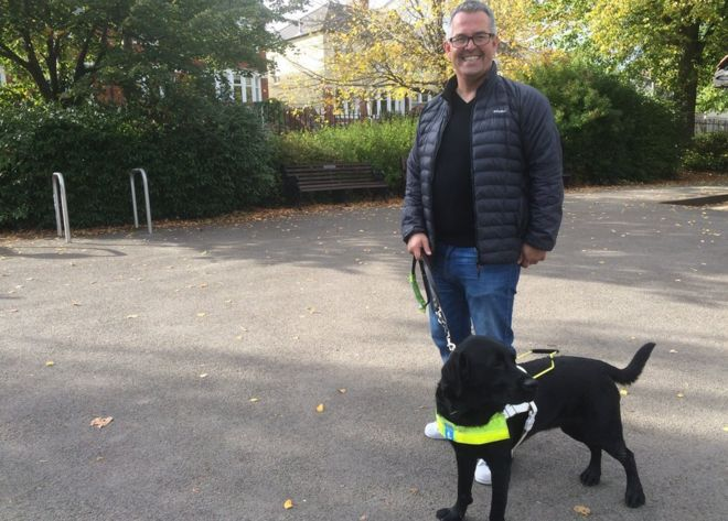 Gareth Davies shown with his guide dog.