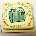 "Plain white fondant covered cake depicting the WTN logo at the centre surrounded by the text ""Witney Talking News 40 Years""."