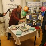 Chairman Peter Bee cuts the cake under the watchful eye of Secretary, Peter Bee, as Radio Oxford presenter, Simon Oliver records his speech.