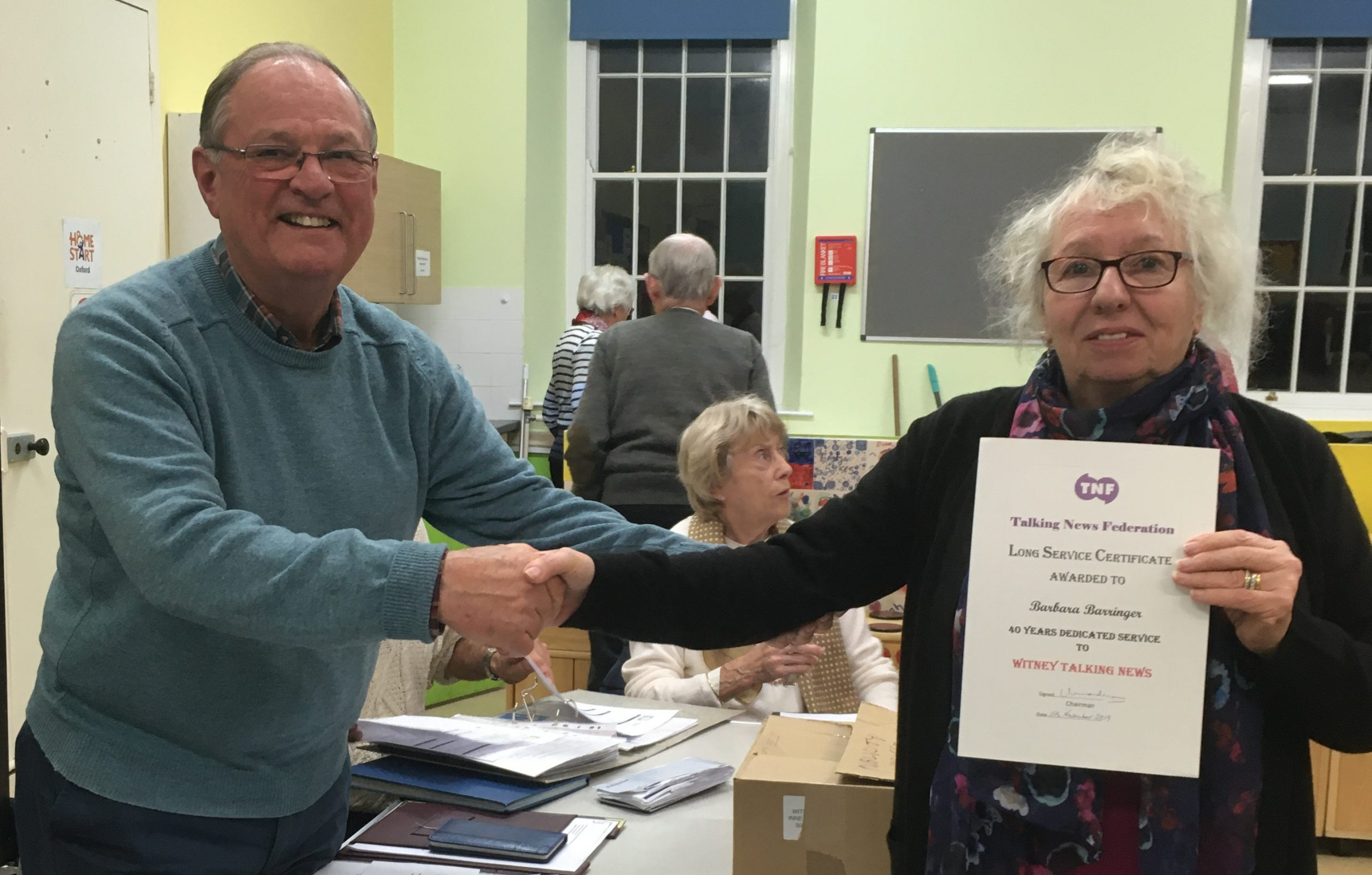 Volunteer Barbara Barringer receives her long service award from chairman Peter Brading.